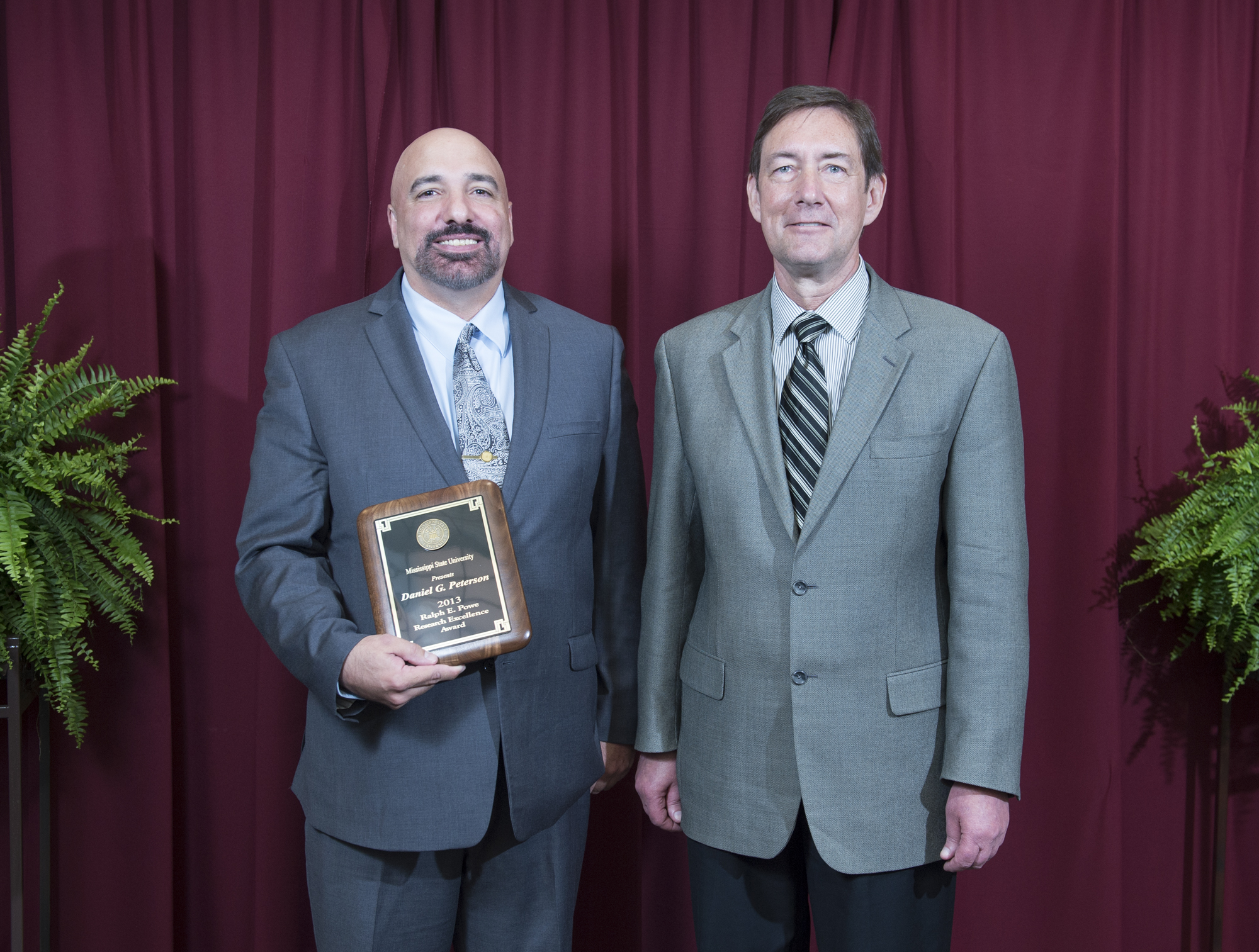 Plant and soil sciences department professor Daniel G. Peterson, left, the winner of the 2013 Ralph E. Powe Research Excellence Award, was congratulated by Greg Bohach, vice president for agriculture, forestry and veterinary medicine.