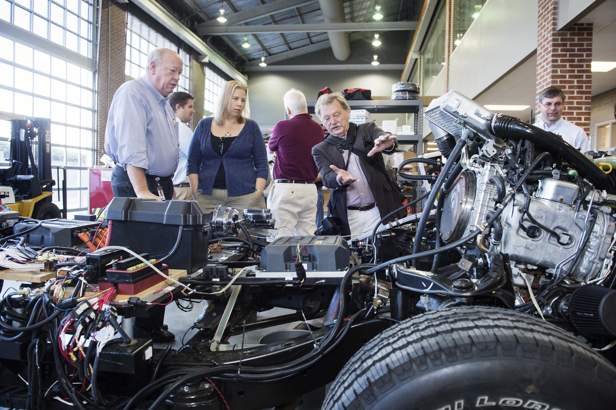 "Zach Rowland, left, of Mississippi State's Center for Advanced Vehicular Systems, looks on with Katy Lusky and Dale Aspy of the Environmental Protection Agency as they discuss the ""Car of the Future"" project which demonstrates leading technology in vehicle performance and energy efficiency."