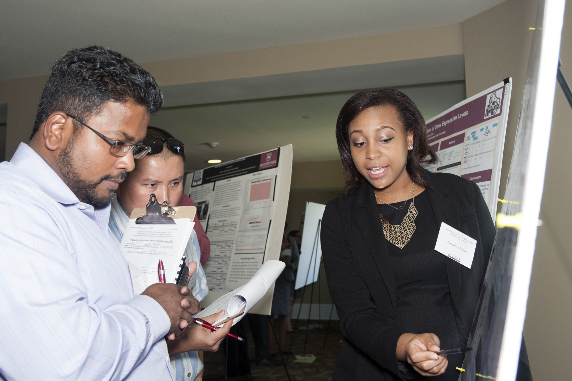 Mississippi State faculty members Raj Prabhu (l) and Thu Dinh look on as freshman Jasmine S. McNair of Ridgeland presented her project during the university's 2015 Undergraduate Summer Research Symposium organized by the Shackouls Honors College.